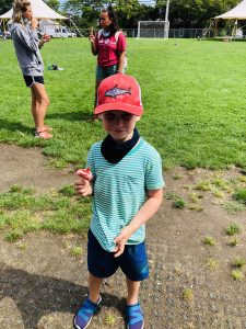 Boy with red hat on the field.