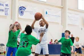 Youth shooting a basket ball over defenders